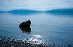 A solitery boulder sits in the shallows of Lake Coeur d' Alene on an atmospheric morning.