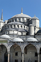 Detail of cascading domes and arcade (revak) surrounding the courtyard, Sultan Ahmed Mosque, or Blue Mosque, 1609-16, by Mehmet Aga, Istanbul, Turkey. The Sultan Ahmed Mosque, commissioned by Sultan Ahmed I, dominates the Istanbul skyline with its cascading domes and six minarets. Built near the Hagia Sophia, it combines Byzantine style with Islamic architecture. The historical areas of the city were declared a UNESCO World Heritage Site in 1985. Picture by Manuel Cohen.