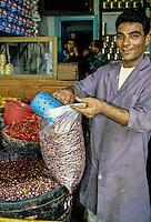 Tunisia.  Tunis Medina.  Wholesale Grocer Omar ben Omar Bagging Olives for a Customer.