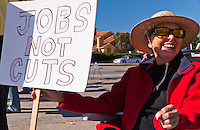 """Cov sits in a lawn chair holding a """"Jobs not cuts"""" sign at the Occupy Orange County, Irvine camp on November 5."""