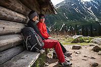 Two female hikers sit outside mountain barn, Tatra mountains, Poland