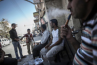 A group of men sit at the entrance of a public bath as they smoke from a water pipe in downtown Manbij, a city located at the northeast of Aleppo province.