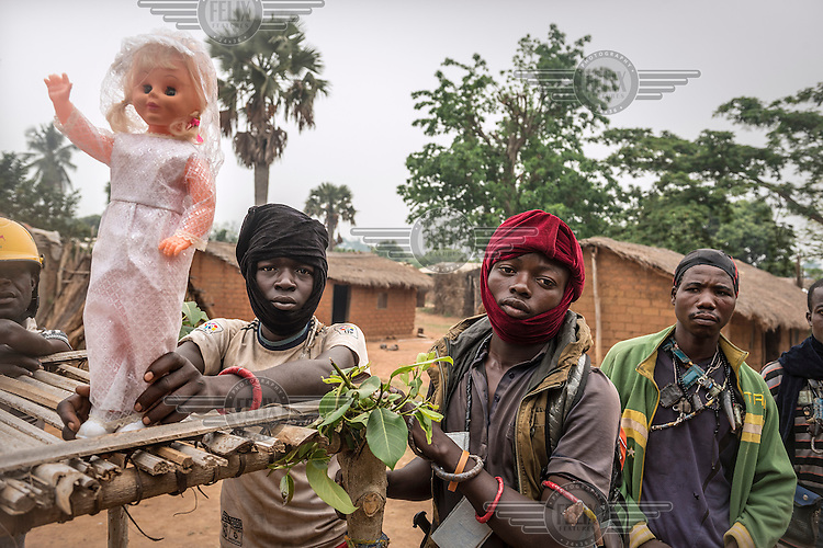 A group of Anti-Balaka fighters holding a blonde doll and drapped in strings of Gris-Gris amulets that contain spells to protect the wearer against bullets and harm. They claim they are defending the Christian side of Boda against the Muslim side while French peace-keepers try to keep them apart.  In 2013 a rebellion by a predominantly Muslim rebel group Seleka, led by Michel Djotodia, toppled the government of President Francios Bozize. Djotodia declared that Seleka would be disbanded but as law and order collapsed the ex-Seleka fighters roamed the country committing atrocities against the civilian population. In response a vigillante group, calling themselves Anti-Balaka (Anti-Machete), sought to defend their lives and property but they then began to take reprisals against the Muslim population and the conflict became increasingly sectarian. French and Chadian peacekeeping forces have struggled to contain the situation and the smaller Muslim population began to flee the country.