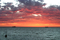 The Cottesloe Beach pylon and ships at anchor with a bright red sunset