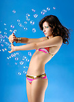Young woman in bikini covering from soap bubbles