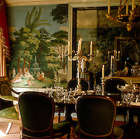 The table is laid for a candlelit dinner in this elegant dining room which has walls covered in exotic trompe l'oeil scenes and mirrored panels