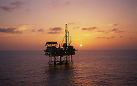 Stock photo of an offshore jack-up drilling rig at sunset.
