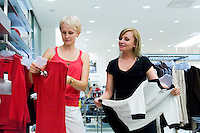 Two women looking and comparing different clothes in shop. Retail store, fashion.