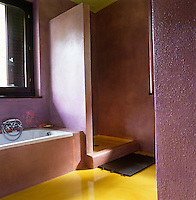 In this bathroom with en-suite shower a glossy yellow floor combines with a metallic pink on the walls to create a colourful impact
