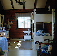 In the naturally dark interior of this 1925 log cabin it was important to paint the furniture white and to use various blue and white fabrics to add pattern and texture