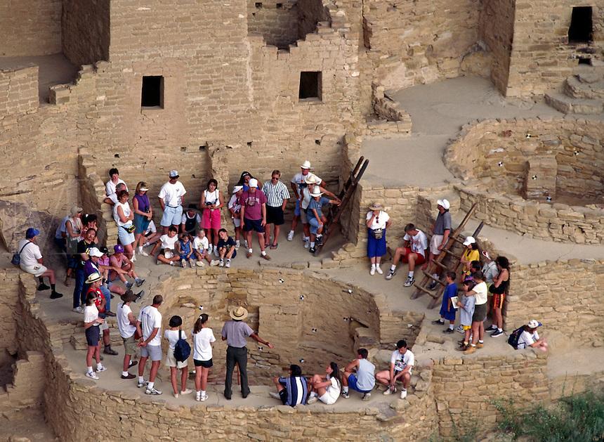 Visitors encircle a KIVA at CLIFF PALACE,  the most extensive ANASAZI ruin of MESA VERDE NP .