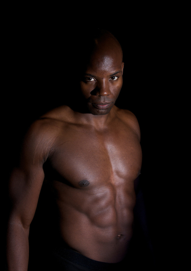 African american body builder emergeing from darkness.