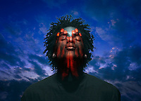 Transparent red hand cover the face of a young Black man with closed eyes under stormy, dark skies.