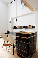 """In this kitchen-diner a dining table, hob and kitchen cupboard are all integrated in the central island which is made of plywood and finished in black linoleum; the dining chairs are the """"Plastic Side Chair"""" design by Charles Eames"""