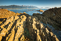 Rock formations of Kaikoura coastline with Kaikouras mountains in background, Kaikoura, Marlborough Region, South Island, East Coast, New Zealand