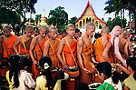 Novices and monks receive alms at Manno temple in Luang Prabang, Laos.