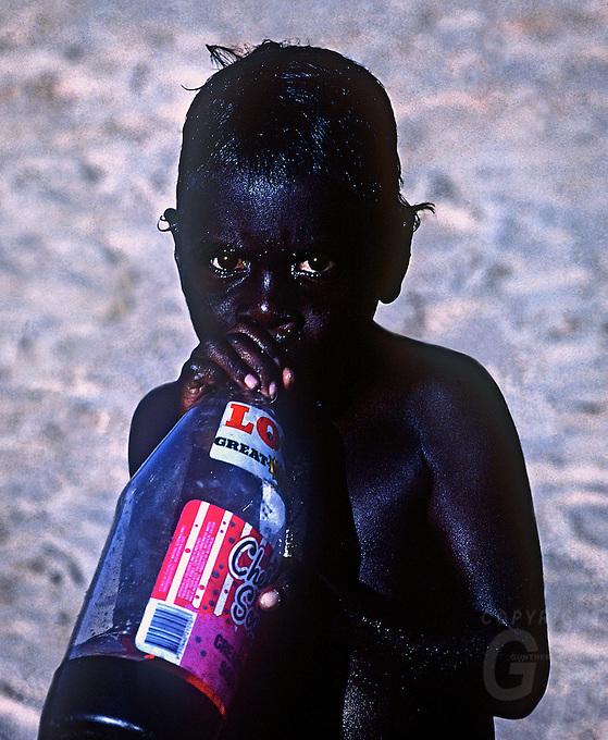 Aboriginal Boy having a drink after a swim in the Ocean,NT Australia