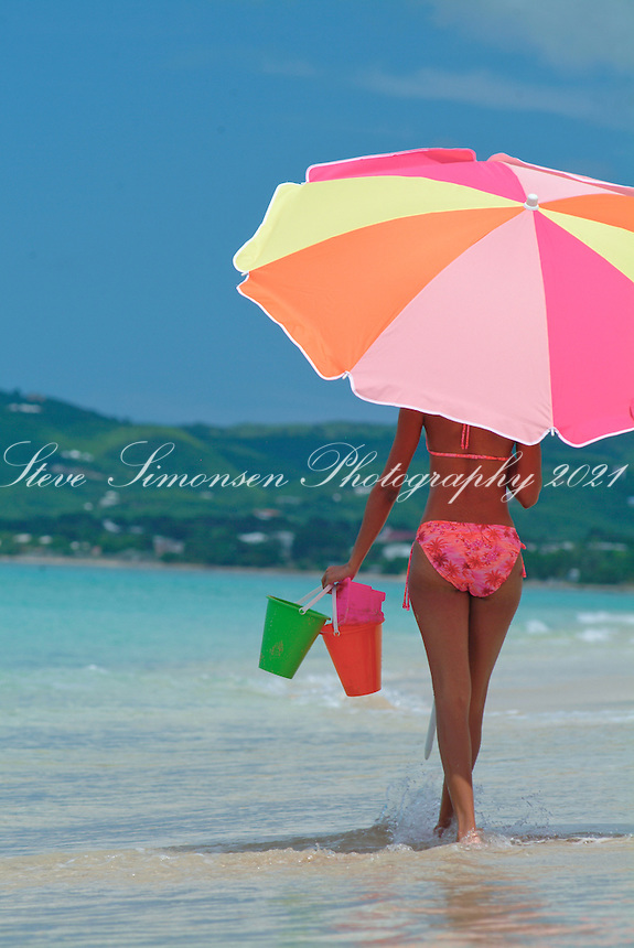 Young woman with beach umbrella and beach toys<br /> Sandy Point, St Croix<br /> U.S. Virgin Islands