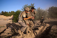 US Army soldiers help a wounded comrade onto a waiting medevac helicopter from Charlie Company, Sixth Battalion, 101st Aviation Regiment in the middle of a firefight near Kandahar. The wounded soldier had shrapnel wounds from a mortar fired at his position.