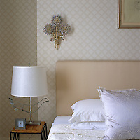 A delicate sconce with glass flowers and brass trimmings hangs on a patterned wallpaper above the bed