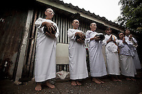 "Mae Chees clad in white robes stand silently in the early morning light at the neighborhood streets as they holds out their alms bowls hoping for food or monetary offerings. Vanished by centuries the lineage of ""Bhikkhu?nii"" (Order of Nuns) has been brought to the ongoing Thai society's debate. White-clad thai nuns, who keep the eight precepts and have their heads and eyebrows shaved are known as the lon-existing ""mae chees"" (low category to call the lay nuns). Females who have turned to religous life, as renunciants, live ostracized and marginalized by the Sangha (Buddhist community) and Thai society, denying them full access to the monastic life as well as rights and support from the government. Today nunhood is not recognized by any asian country belong to the Theravada Buddhist order. Most of the eight precept holders live in temples run by male abbots, at the shadow of the monks; with the exceptional existence of a few para-monastic institutions as the Sathira Dhammasathan meditation centre, where ""mae chees"" are not allow to held a temple, but not denied to practice the spiritual life."