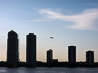 A Goodyear blimp climbs in the late-afternoon sky behind the silhouettes of condominium buildings on Miami's Brickell Avenue.