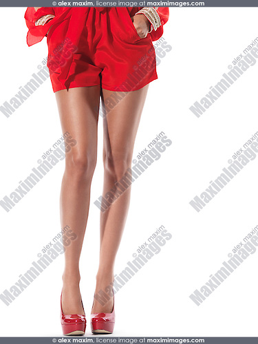 Closeup of long legs of a young woman wearing sexy red clothes and red high heel shoes isolated on white background