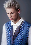 blonde boy with piercings looking away from the camera. He is wearing a knitted vest.