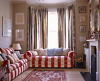A Victorian room is furnished in contemporary style with the use of bold striped fabric
