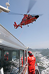 A United States Coast Guard HH-65C Dolphin helicopter lowers a rescue basket to the deck of a Coast Guard Auxiliary vessel. The helicopter and crew, based at U.S. Coast Guard Air Station San Francisco, was on a practice mission with the Coast Guard Auxilary to maintain search and rescue proficiency.