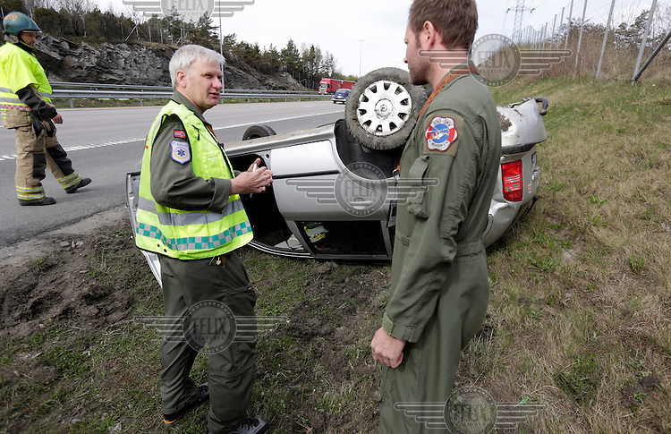 Anesthesiologist Hallstein S&oslash;reb&oslash; discuss with rescue paramedic Lars Markengbakken at an accident scene.  Crew from Norwegian Air Force 330 squadron, flying Westland Sea King helicopter. The core mission of the squadron is SAR (search and rescue), but they also fly HEMS (Helicopter Emergency Medical Service), complementing the civilian air ambulance service, and use a car in their local area. <br /> This crew fly out of Rygge Air Station, Norway.