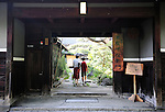 A woman and child walk through the entrance of Sakahan sake brewery in Mukune village, Osaka, Japan on July 24 2008. The brewery was established in 1826...Photographer: Robert Gilhooly