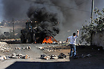A Palestinian protester throws stones at Israeli bulldozer on the sidelines of a demonstration against the expropriations by Israel in the West Bank village of Kafr Qaddum, near Nablus, on November 30, 2012. Photo by Nedal Eshtayah