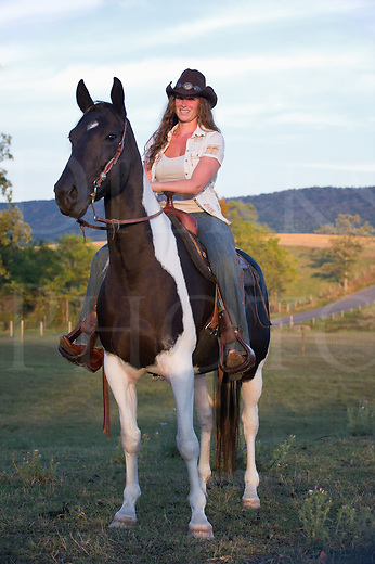 Country woman on horseback riding in the last golden yellow light of day, purebred black and white American paint horse. Nikon D3s, 70-200.