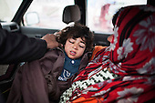 ARBAT, IRAQ: A sick child is put in a car to be taken for medical attention from a refugee camp on the outskirts of Arbat in the semi autonomous region of Iraqi Kurdistan. ..Refugees from Syria, most of whom are Kurds, have been arriving at camps in Kurdistan trying to escape the continuing conflict.  Arbat is located approximately 20 kilometres away from Sulaimaniyah...Photo by Ali Arkady/Metrography.
