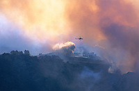 870000345 a los angeles county fire fighting helicopter performs aerial retardant drop on homes directly in the burn path of the topanga fire in the hills above the san fernando valley in southern california