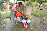 A woman pours out water she has taken from a well in the Guatemalan village of Santa Elena, located in the Peten region along the Salinas River where it forms a border with Mexico.