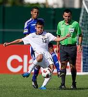 Dillon Serna (13) of the United States clears the ball away from Adrian Diz (4) of Cuba during the first day of the group stage at the CONCACAF Men's Under 17 Championship at Catherine Hall Stadium in Montego Bay, Jamaica. The United States defeated Cuba, 3-1.