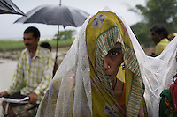 People from the Parsi caste shelter from a rainstorm along an embankment surrounded by land flooded by the river Ghaghara...Flooding along the River Ghaghara on July 29th forced the evacuation of people from the villages of Para and Reta in Barabanki District, Uttar Pradesh state. Residents, all of them from the Parsi scheduled caste, are now living in make-shift homes on an embankment 1km away. Three weeks later, many of their homes are still either beneath water or are uninhabitable. Crops have been destroyed. The government have provided essential rations of rice, salt, pulses and kerosine. Unicef supports a Barabanki district health department mobile health camp by providing medicines and funding. The health camp proved DPT, BCG and measles vaccination for children as well as general health check-ups for adults and children. Unicef has also disitributed ORS (Oral Rehydration), clorine tablets, jerry-cans and tarpaulin sheets to the displaced Parsi community. ..Flooding, begining at the end of July 2007, has ravaged 14 districts in India's northern Uttar Pradesh state. Crops have been destroyed, people left homeless and communities isolated. The districts of Barabanki and Gorakhpur are among those still suffering rainfall. Together with the government, Unicef is providing relief to affected communities, many of whom are without the resources to adequately cope with the situation. Supplies of chlorine tablets, ORS (Oral Rehydration Salts), tarpaulin and mosquito nets have been distributed by Unicef among affected communities. With the support of local administrations, Unicef has begun the construction of eco-san latrines in areas that have suffered flooding. Information on hygiene and sanitation has been provided in an effort to stem the threat of water-bourne disease. Unicef and the government have joined forces to send doctors into flood-affected areas. These mobile health-units provide consultation and treatment as well as medicine to those suffering in the flo