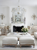 In the drawing room a large crystal chandelier is suspended above an ottoman covered in white linen with a pair of matching footstools