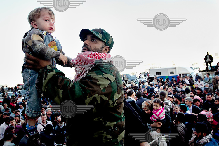 A Libyan soldier holds a child as he helps to process thousands of Syrian refugees as they try to escape Libya at the port in Benghazi. Syria has sent ships to pick up their citizens, but there's only room for 1000 in each. Today they sent three ships and tomorrow there will be more. The Syrian government promises that all Syrians will be evacuated. On 17 February 2011 Libya saw the beginnings of a revolution against the 41 year regime of Col Muammar Gaddafi.