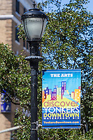 A banner promoting the Yonkers Downtown Waterfront Business Improvement District (BID) hangs from a lamppost in Yonkers, New York.