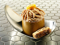 A modern Japanese cake with a pattered chocolate case and piped chestnut puree with cumquat sauce, in a modern designer dish