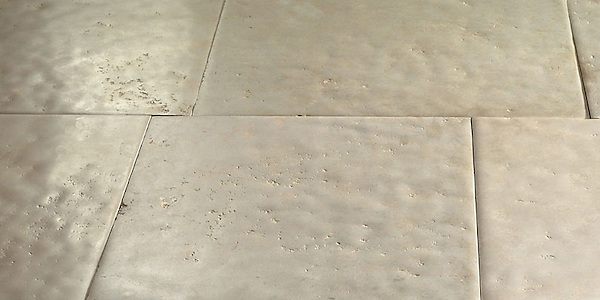 Solid Natural Limestone Tiles of a very consistent composition, with straight cut, slightly pillowed edge, naturally undulated, high honed surface. Shown in a highly variegated Beige. <br />