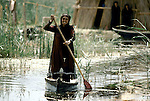 Marsh Arabs. Southern Iraq. Circa 1985. Marsh Arab woman standing in boat rowing between traaditional reed island homes. MARSH ARAB WOMAN, DRESSED IN TRADITIONAL CLOTHING, STANDING UP IN WOODEN CANOE PADDLING IT FORWARD WITH OAR,