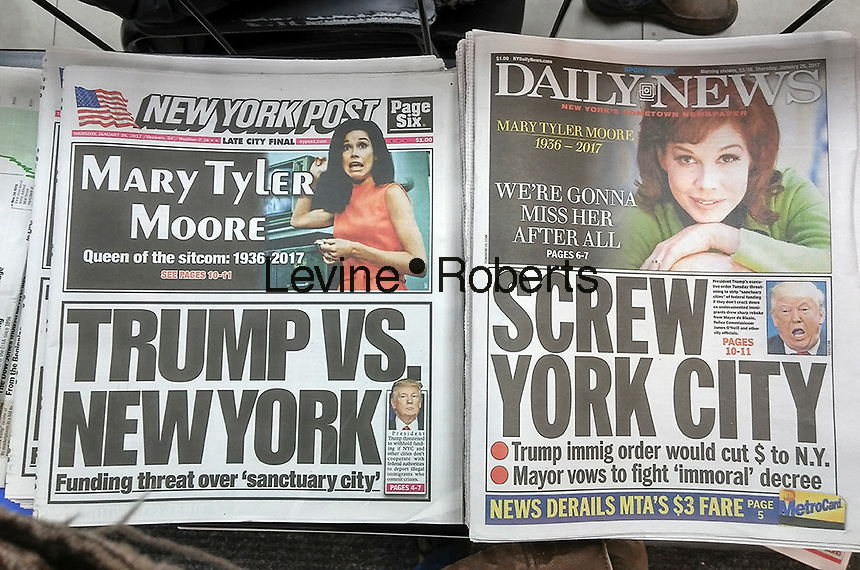 """New York newspapers on Thursday, January 26, 2017 report on President Donald Trump's executive order on immigration and its effect on """"sanctuary cities"""".  In addition the top of each paper reports on the death of Mary Tyler Moore. (© Richard B. Levine)"""