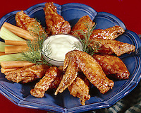 """Hot Chicken wings """"Buffalo Wings"""" with blue cheese dressing and vegetable sticks on the side"""