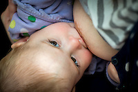 A close-up of a baby breastfeeding.<br /> <br /> Image from the &quot;We Do It In Public&quot; documentary photography project collection: <br />  www.breastfeedinginpublic.co.uk<br /> <br /> Dorset, England, UK<br /> 17/04/2013