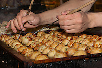 Chef Ryota Akai of Japan turns takoyaki during a demonstration of takoyaki cooking at Mitsuwa Market in Costa Mesa, California.  The chef used chopsticks to delicately poke and turn each takoyaki ball.  While this sounds slow, he touches each ball for only a tiny fraction of a second, making this one of the shots I'm proudest of.