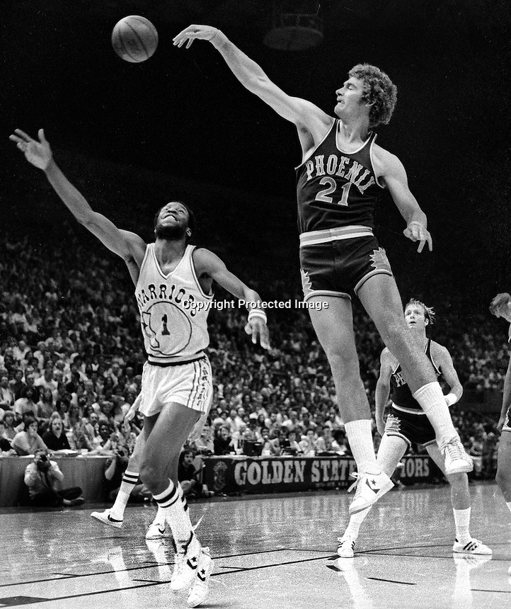 Phoenix Suns Dennis Awtrey blocks shot of Golden State Warrior Gus Williams during playoff game 1976.<br />